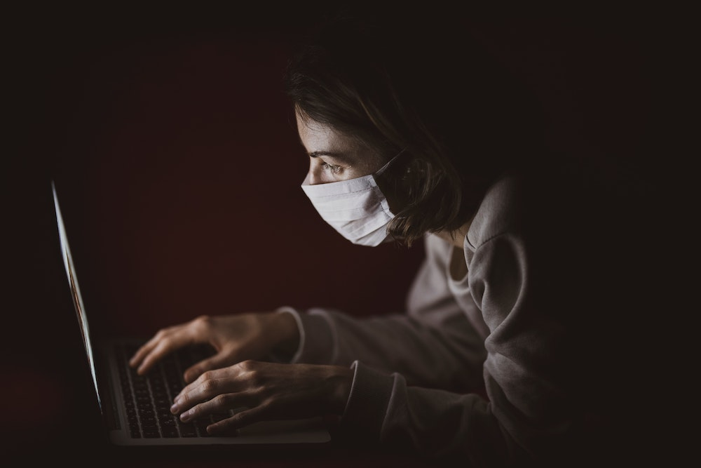 woman searching symptoms for covid-19 sore throat on laptop
